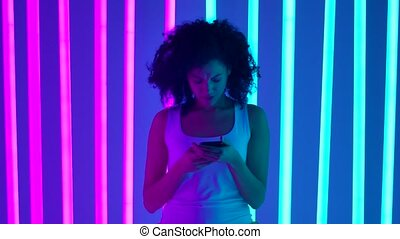 Portrait of a young beautiful woman who writes text messages on her phone with an enigmatic smile. A beautiful girl with curly hair and a white Tshirt poses in the studio surrounded by bright pink and blue neon tubes. Slow motion.