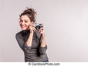 Portrait of a young beautiful woman with camera in studio.