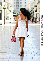 Portrait of a young black woman, afro hairstyle, walking...