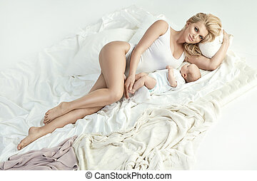 Portrait of a young blond mother with a newborn baby