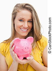 Portrait of a young blond woman holding a piggy-bank