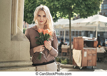 Portrait of a young blond woman with a bunch of roses