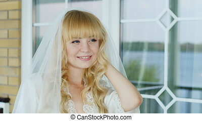 Portrait of a young blonde bride - smiling, looking into the distance
