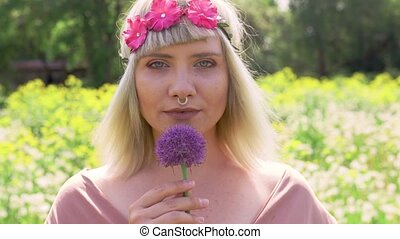 Portrait of a Young blonde hippie woman with nose ring and magenta pink flower band in hair holding onion violet flower and looking straight at the camera