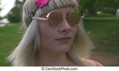 Portrait of a Young blonde hippie woman with nose ring and magenta pink flower band in hair wearing mirror glasses - Sunny green field in the background in bokeh shallow depth of field dop.