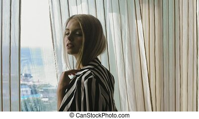 Portrait of a young blonde in a striped jacket standing near a panoramic window