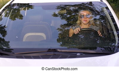 Portrait of a young blonde in sunglasses in the car behind the wheel.