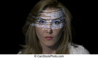 Portrait of a young blonde woman computer programmer coding while binary data characters are projected on her face