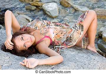 Portrait of a young blue-eyed woman lying on a rock