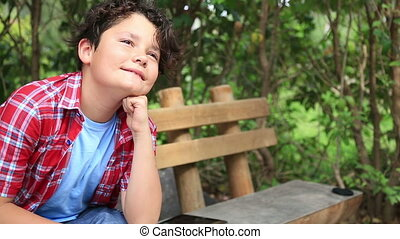 Portrait of a young boy day dreaming in nature