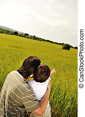 Portrait of a young boy showing some thing intersting to his father against natural scene