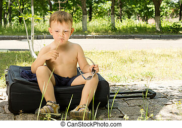 Portrait of a young boy sitting on a travel bag