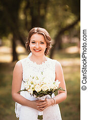 portrait of a young bride on the background the park