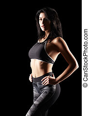 Portrait of a young brunette sporty fitness woman on black