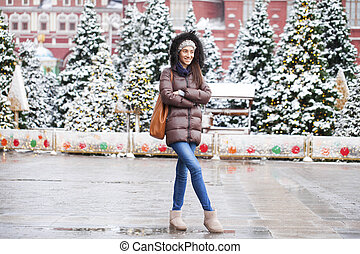 Portrait of a young brunette woman in down jacket