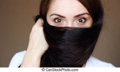 Portrait of a young brunette woman who is covering her face with hair. Beautiful dark brown eyes of the girl express different emotions, look at the camera.