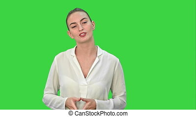 Portrait of a young business woman presenting something by a hand on a Green Screen, Chroma Key.