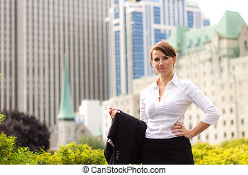 Portrait of a young business woman with city background