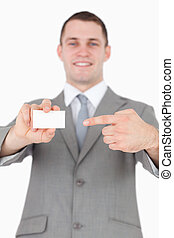 Portrait of a young businessman pointing at a blank business card against a white background
