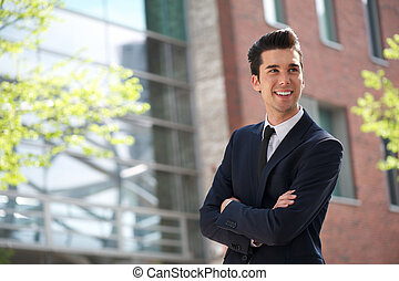 Portrait of a young businessman smiling outdoors
