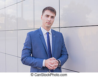 Portrait of a young businessman standing over blurred background