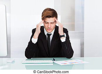 Young Businessman Suffering From Headache In Office
