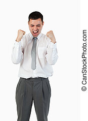 Portrait of a young businessman with the fists up against a...