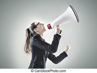 Portrait of a young businesswoman yelling over the megaphone