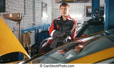 Portrait of a young car mechanic in overalls in a car...