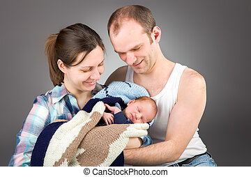Portrait of a young caucasian couple with three-month old...