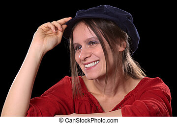 Portrait of a young Caucasian woman smiling wearing a red shirt and a blue Gatsby cap (Selective Focus, Focus on the left eye and the left side of the face)