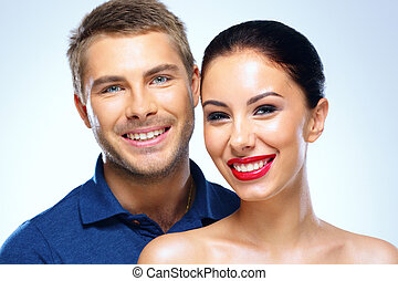 Portrait of a young cheerful couple on blue background