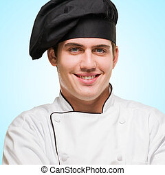 Portrait Of A Young Chef With Hands Folded against a blue...
