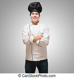 Portrait Of A Young Chef With Hands Folded against a grey...