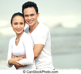 young couple at the beach - Portrait of a young couple at...