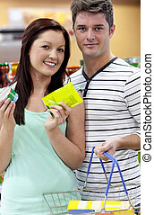 Portrait of a young couple buying cans standing in a grocery shop and smiling at the camera