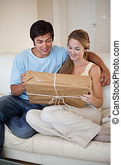 Portrait of a young couple looking at a package