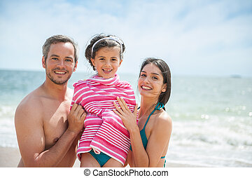 Portrait of a young couple posing in swimsuits with their daughter
