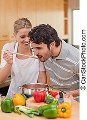 Portrait of a young couple preparing a sauce