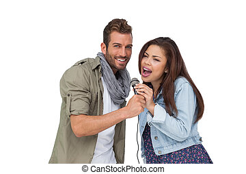 Portrait of a young couple singing into microphone