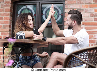 Portrait of a young  couple sitting down at a cafe terrace