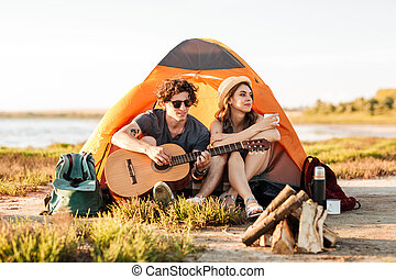 Portrait of a young couple sitting with guitar near bonfire