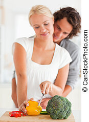 Portrait of a young couple slicing pepper