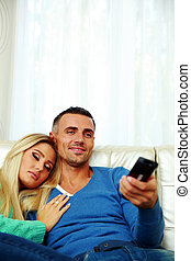 Portrait of a young couple watching TV at home