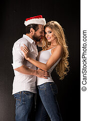 Portrait of a young couple with Santa hat looking into the camera