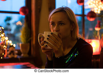 Portrait of a young cozy with cup of coffee, cookie and Christmas lights and pine branch.