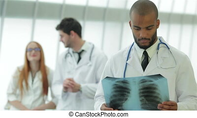 Portrait of a young doctor with x-ray in hands on background of two colleagues