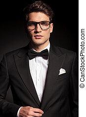 young elegant man closing his jacket