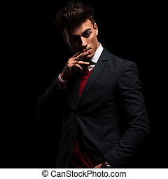 young elegant man in suit and tie smoking