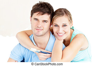 Portrait of a young enamored couple painting their new room